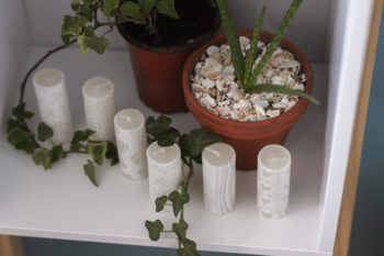Small white candles by plant