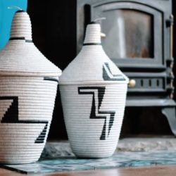 2 uduseke storage baskets by a fireplace