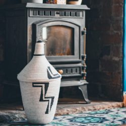 Agaseke storage basket in front of fire place on blue tiles