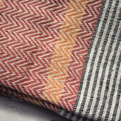Close up of ethical terracotta red throw