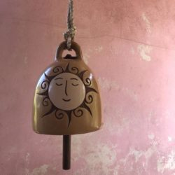 Hanging ceramic garden bell with smiling sun pattern