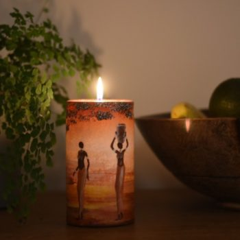 Lit hand painted candle with 2 ladies walking into african sunset