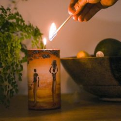 hand reaching to light a hand painted candle with 2 ladies walking into african sunset